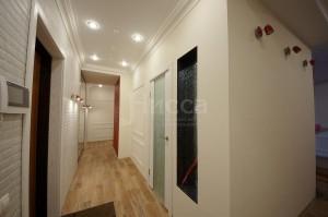 Сравнительно узкий коридор визуально расширен хорошим освещением и светлой отделкой стен