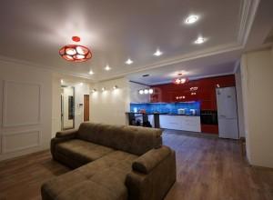 Огромная гостиная после ремонта, с модной сине-бордовой кухонной зоной