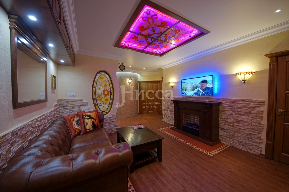 Гостиная с камином и диваном для семейного отдыха.